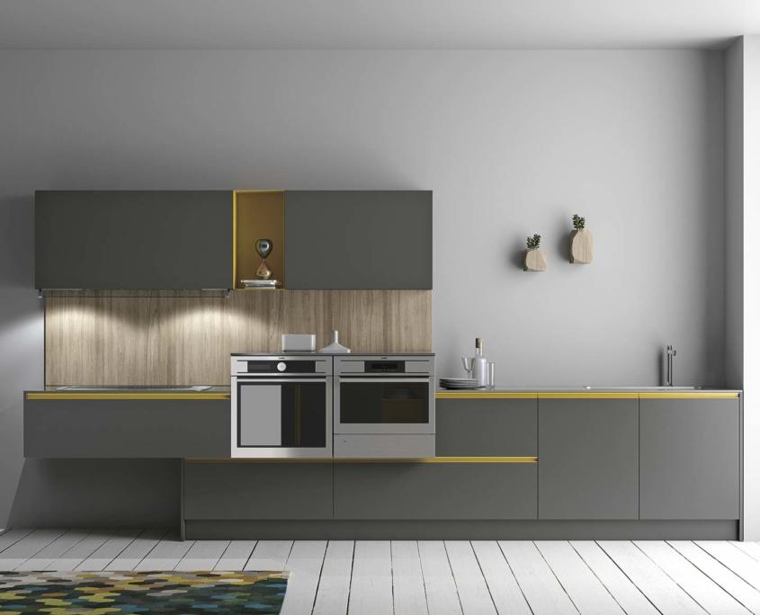 La asimetría toma cuerpo en esta cocina donde se juega con el color vivo del amarillo en contraste con el griggio piombo.